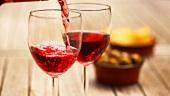 Rotwein einschenken, im Hintergrund eingelegte Oliven & Chips