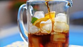 Pimms being poured into a jug of ice cubes