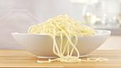 Abgetropfte Spaghetti in eine Schüssel geben