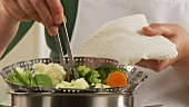A steamer filled with vegetables being removed from a pot