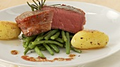 Beef fillet wrapped in bacon (fillet mignon) with beans and potatoes