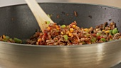 Minced meat being mixed in a pan with diced vegetables