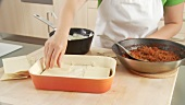 Lasagne sheets and minced meat sauce being layered in a baking dish