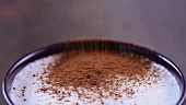 Milk foam being sprinkled with cocoa powder