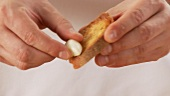 Toasted baguette slices being rubbed with garlic