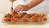 Baguette slices being topped with a tomato and basil mixture