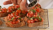 Bruschetta being sprinkled with pepper