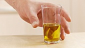 A glass of olive oil being taken off the work surface