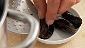 Geschlossene Miesmuscheln aus dem Topf entfernen
