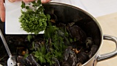 Chopped parsley being added to mussels