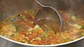 Minestrone being scooped out of a pot with a ladle