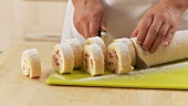 Strawberry cream swiss roll being sliced
