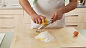 Lemon zest being grated and added to dough ingredients