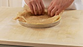 Shortcrust tart base being lined with baking paper and weighed down with legumes