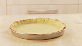 Baked shortcrust tart base in the dish