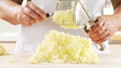 Cooked mashed potatoes being spread on a work surface