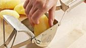Gekochte Kartoffeln durch eine Kartoffelpresse drücken