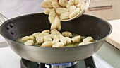 Gnocci being added to a pan of melted butter and sage