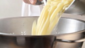 Cooked pasta being drained
