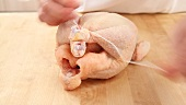 A whole chicken being tied with kitchen twine