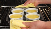 Creme caramel being removed from the oven