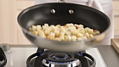 Croutons being roasted in a pan