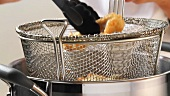 Fried fish fillets being removed from a frying basket
