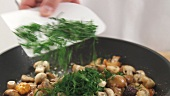 Fresh herbs being added to fried mushrooms