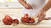 Cooked lobster being served with butter and lemon