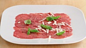 Beef carpaccio being sprinkled with grated parmesan