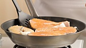 Salmon steaks being fried (German Voice Over)