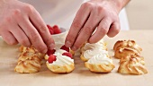 Profiteroles being filled with cream and raspberries