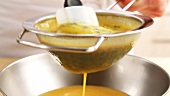Passion fruit purée being sieved