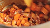 Roasted vegetables being braised in red wine