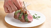 A rack of lamb with a herb crust being prepared (German Voice Over)