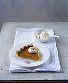 Pumpkin pie with a dollop of cream