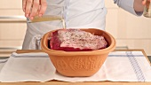 Roast beef being prepared in a clay cooking pot (German Voice Over)