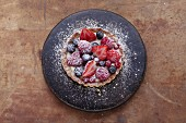 Shortcrust pastry tart being filled with curd cheese and berries (stop motion)