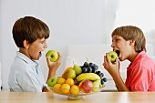 Two boys biting into apples