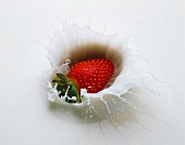 A strawberry falling into milk
