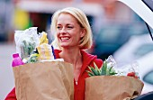 Young, smiling woman carrying bags of shopping