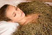 Young woman in hay bath