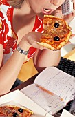 Woman eating pizza at the office