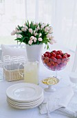 Set table with flowers, strawberries & lemonade