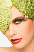 Young woman with savoy cabbage leaves on her head