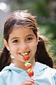 Girl eating a vegetable skewer