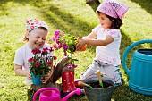 Zwei Mädchen mit Blumen im Garten