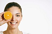 Young woman with a slice of orange