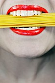 Woman with uncooked spaghetti in her mouth