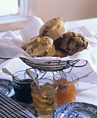 Three Assorted Muffins in a White Napkin with Assorted Jams and Jellies